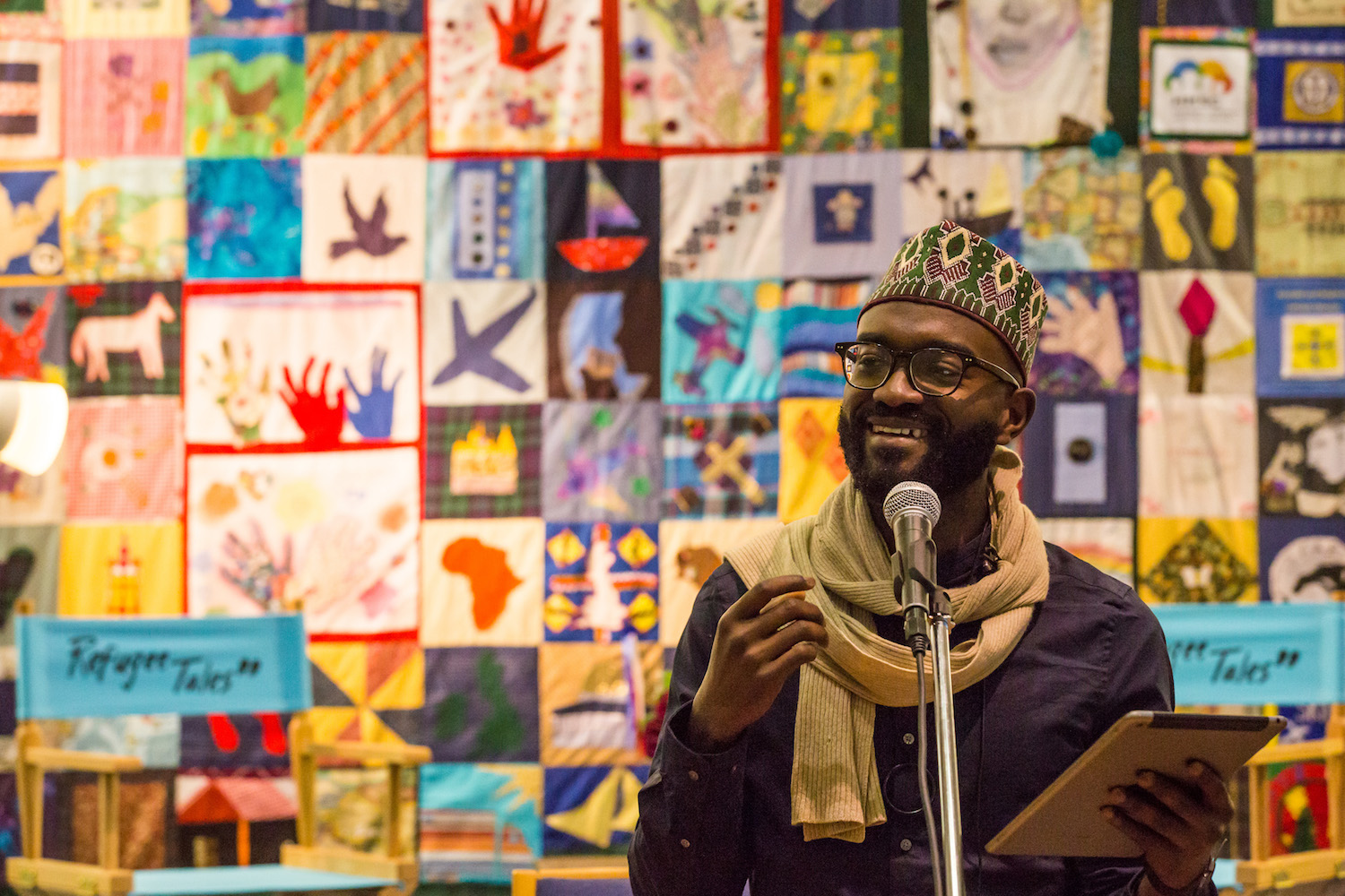 Poet, playwright and writer Inua Ellams reading for Refugee Tales in front of quilt made by Gatwick Detainees Welfare Group Quilt presented by Andrea Luka Zimmerman in The London Open 2018. Courtesy Gatwick Detainees Welfare Group and Refugee Tales. Photo by Chris Orange