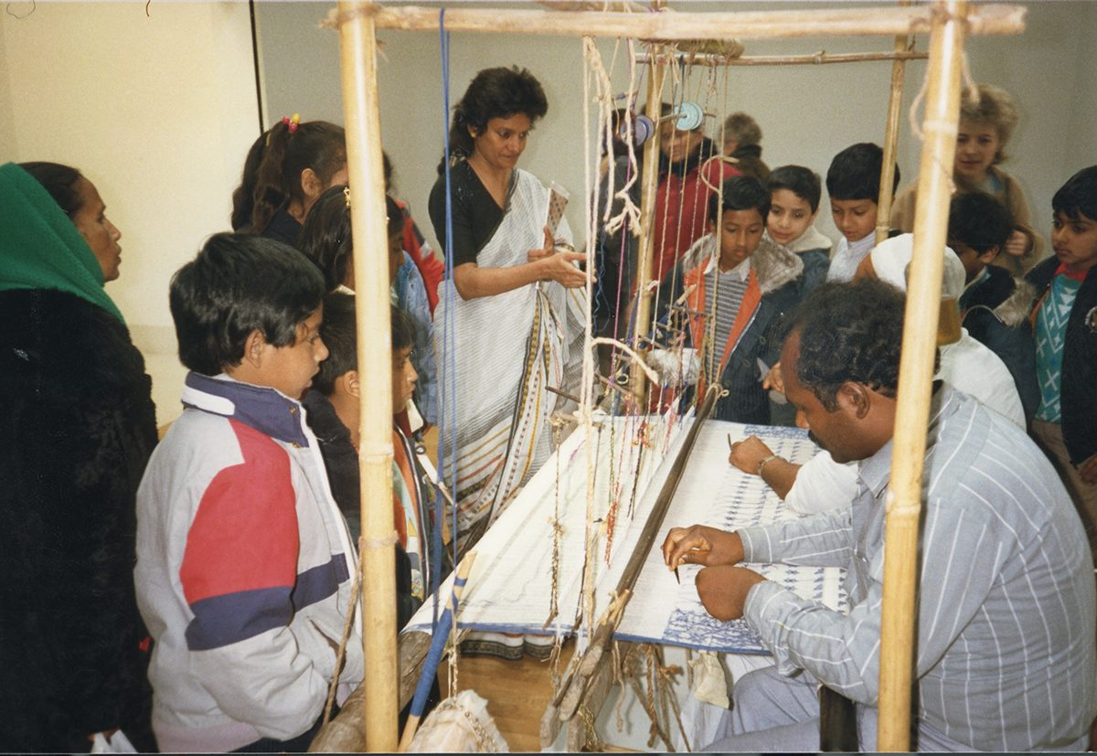 Children taking part in workshops with master weavers Haji Kafiluddin Bhuiya and Nurul Islam during the exhibition Woven Air: The Muslin and Kantha Tradition of Bangladesh, 4 March – 1 May 1988, Whitechapel Gallery C/o Whitechapel Gallery Archive.