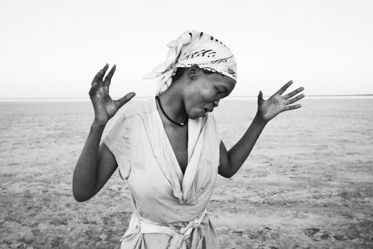 Margaret Courtney-Clarke, Singing the Rain, Selma Jacobs performs a traditional Rain Dance across the barren Omongwa ('Salt') Pan. Aminuis, Namibia, 2019. Courtesy the artist and Prix Pictet